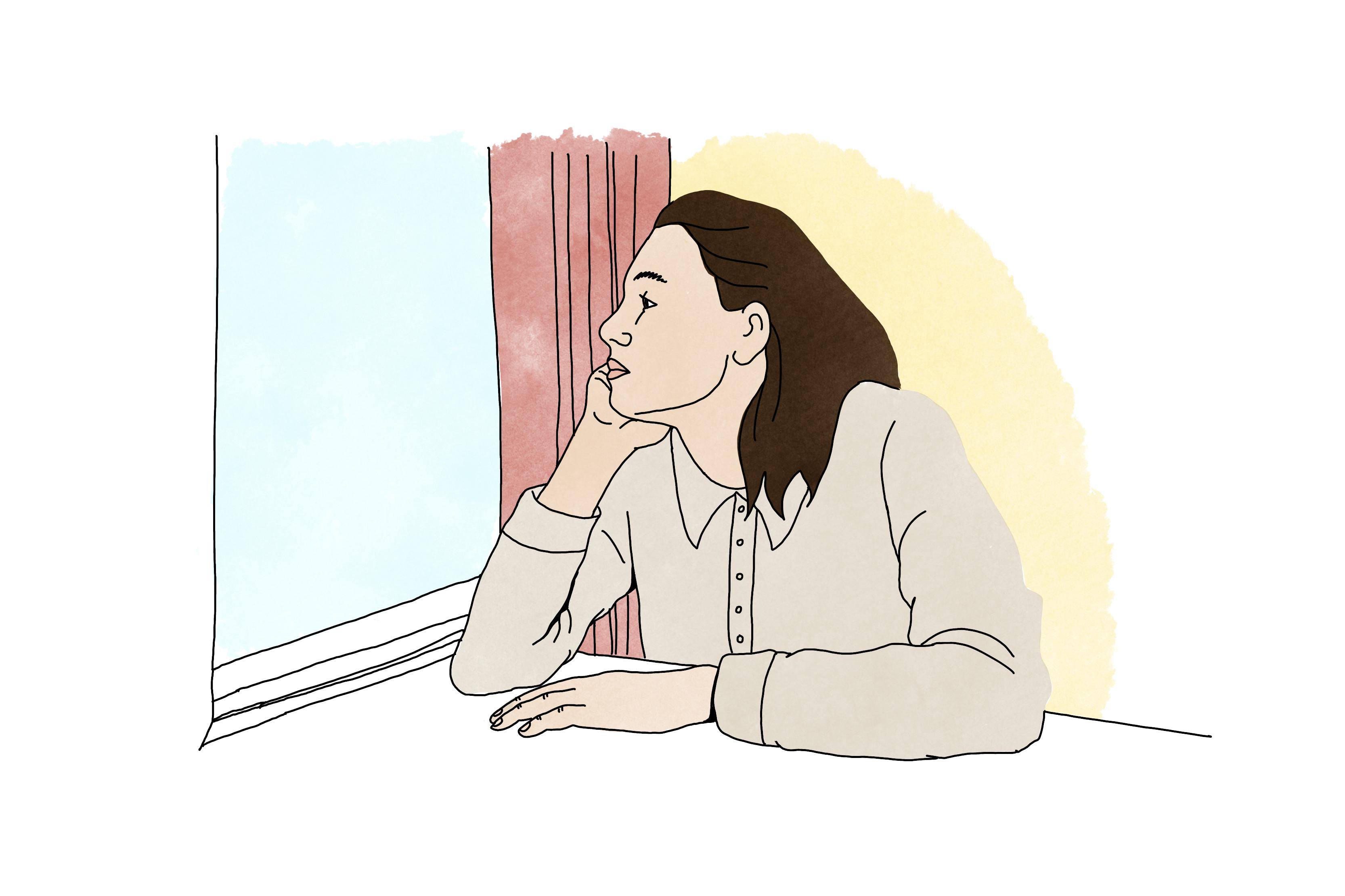 En person sitter och ser ut genom ett fönster.